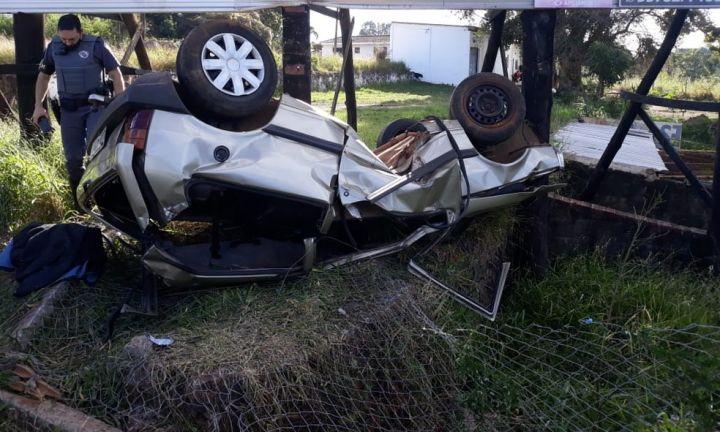 Motorista invade terreno, bate em placa e capota